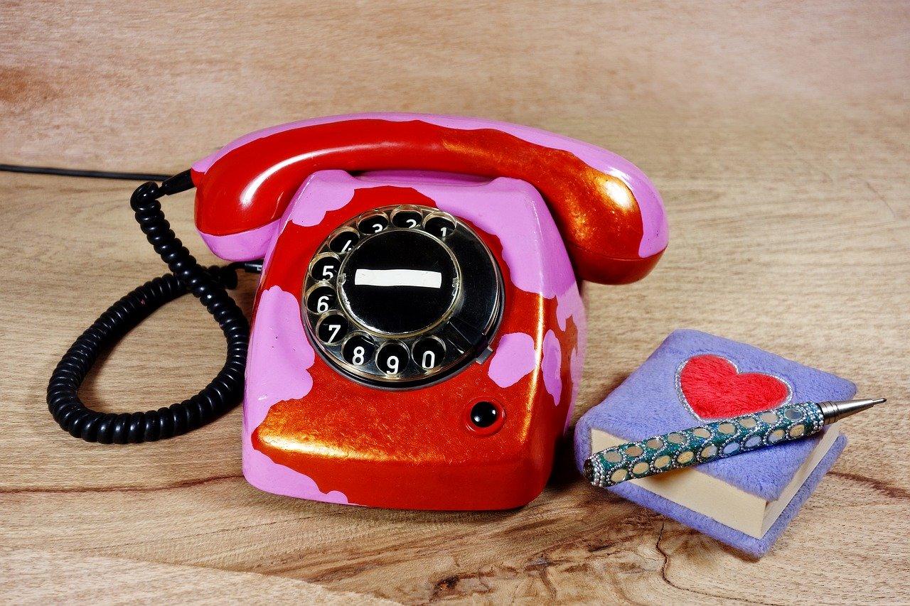 Téléphone rouge et rose et carnet violet avec coeur