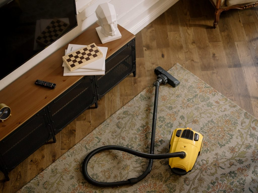 Aspirateur jaune posé sur un tapis