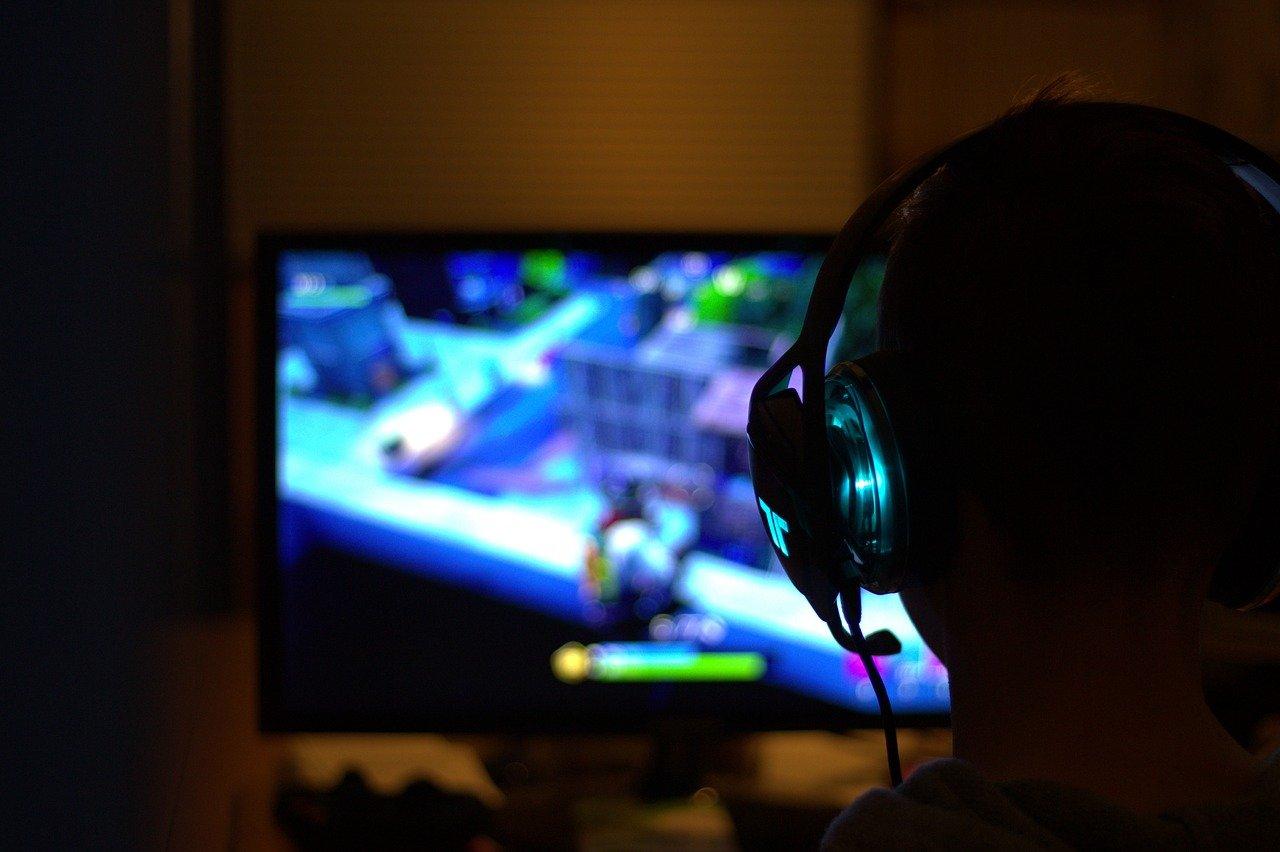 Joueur avec casque jouant à fortnite dans la nuit