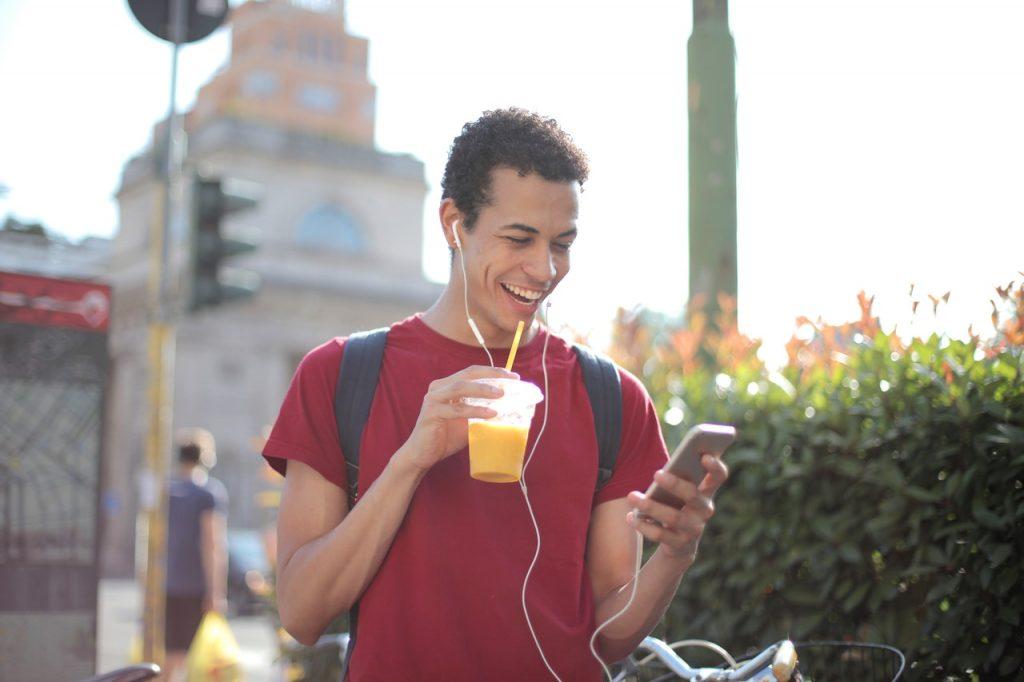 Homme buvant un juste de fruit pressé et lisant message avec écouteur dans les oreilles