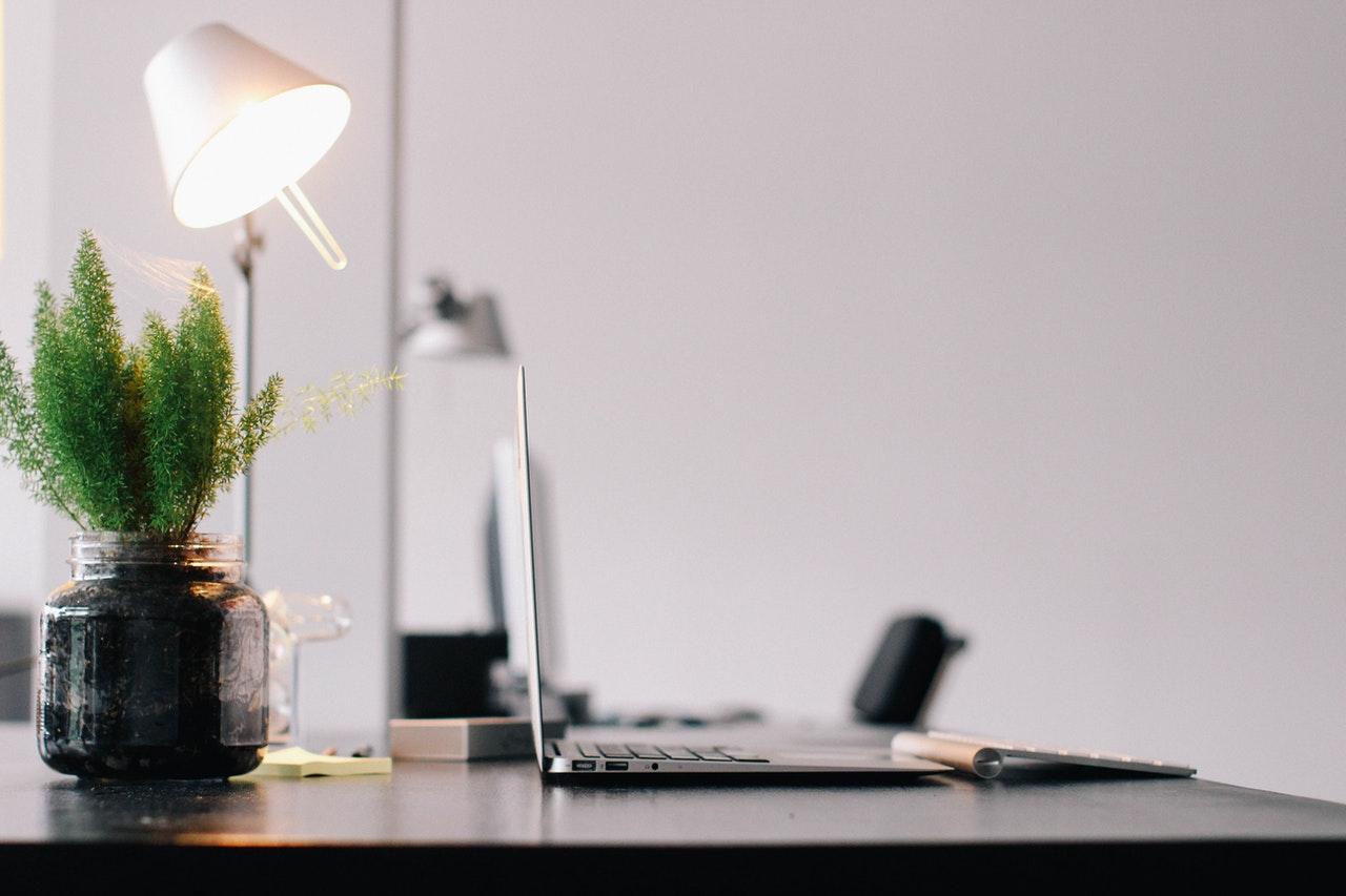 ordinateur macbook posé sur bureau avec lampe et plante