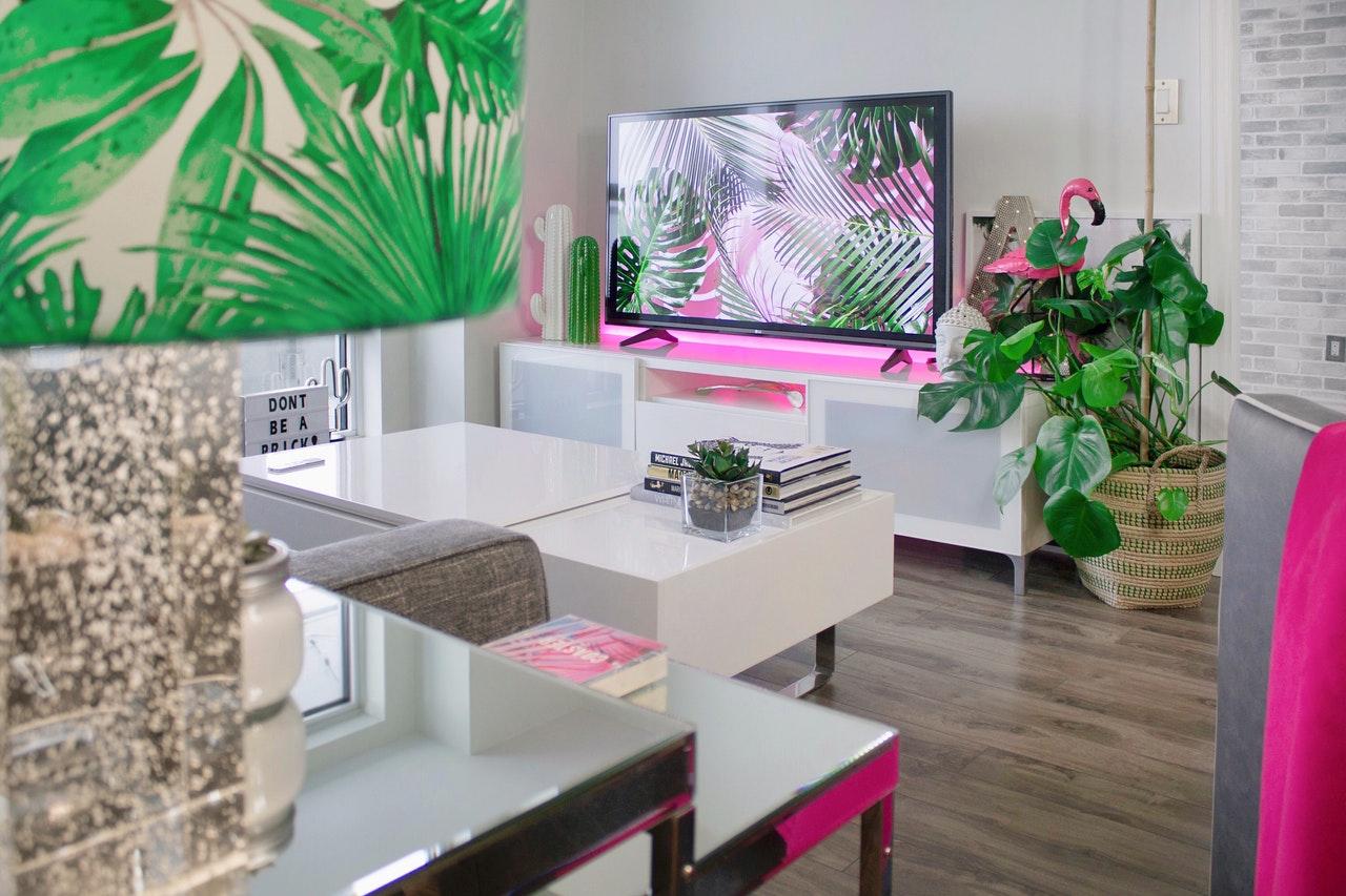 Salon avec mobilier moderne et lumière led rose sous la télé