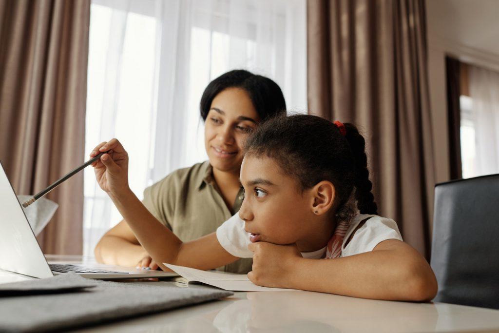 Mère et fille travaillant sur un ordinateur, faisant ses devoirs