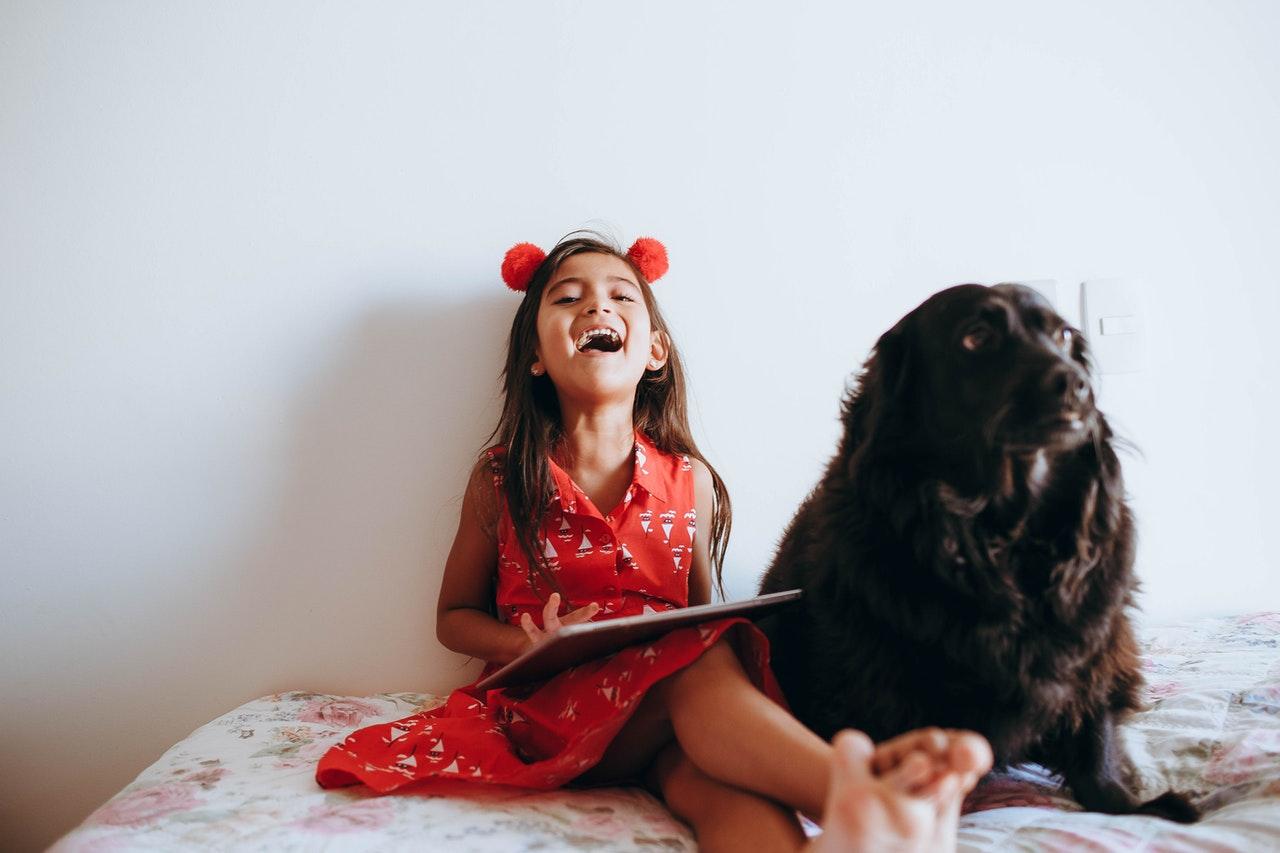 Petite fille assise à côté de son chien sur un lit, riant et su une tablette
